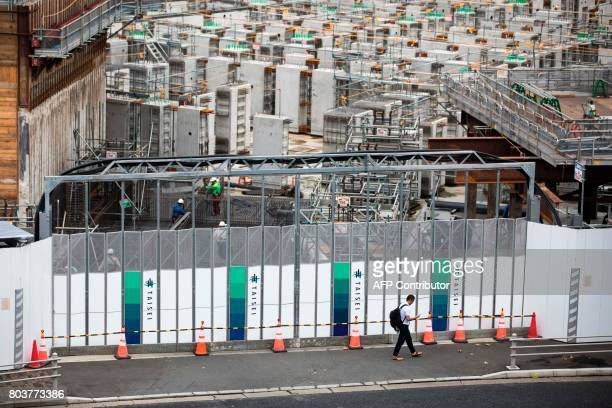 A man walks past the construction site for the National Stadium venue for the upcoming Tokyo 2020 Olympics in Tokyo on June 30 2017 The International...