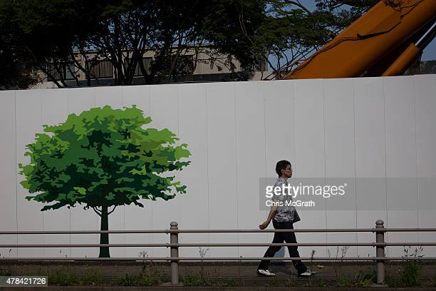 A man walks past the construction site for the new National stadium and the planned main site of the Tokyo 2020 summer Olympics on June 25 2015 in...