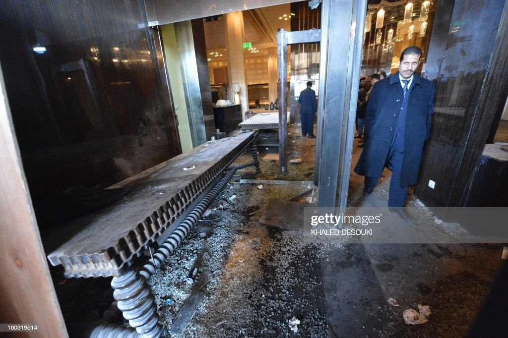 A man walks past the damage to the lobby of the Semiramis Intercontinental Hotel after it was vandalized when protestors stormed the entrance last night, in central of Cairo on January 29, 2013. Egypt's military chief warned that the political crisis sweeping the country could lead to the collapse of the state, as thousands defied curfews and the death toll from days of rioting rose to 52.