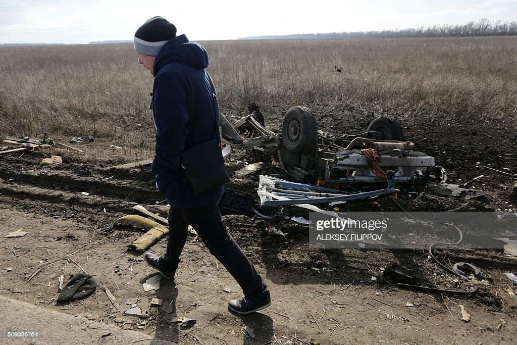 A man walks past the debris of a passenger minibus after it hit a mine near Marinka on February 10, 2016. Three people were killed on February 10 when a passenger minibus hit a mine in separatist eastern Ukraine during a relative calm in fighting in the 21-month war. / AFP / ALEKSEY FILIPPOV
