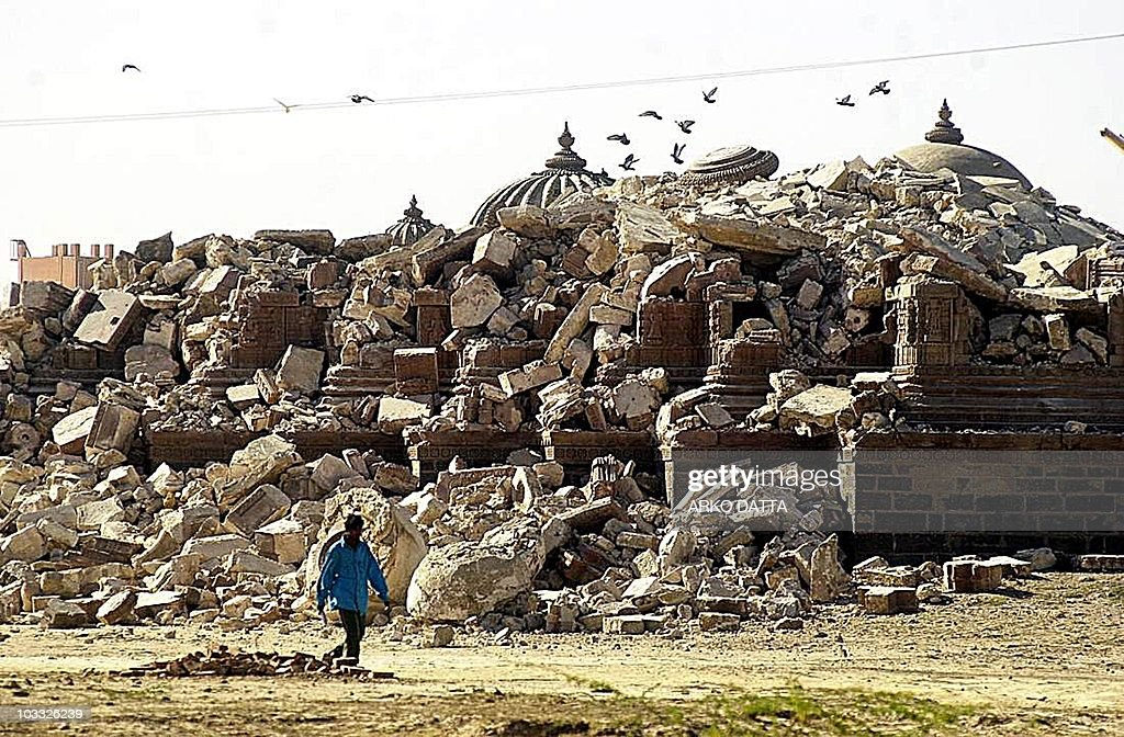 A man walks past the debris of an historical religious monument that collapsed in Bhuj town in Gujarat 31 January 2001 in a massive earthquake that...