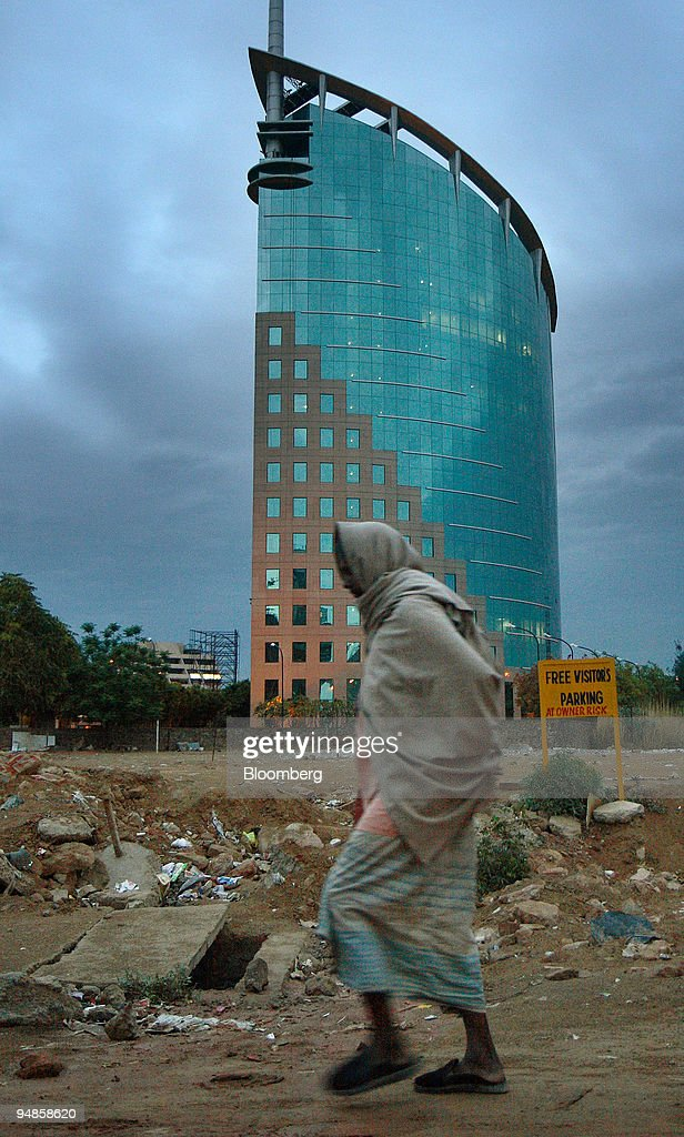 A man walks past the DLF Ltd Gateway tower in Gurgaon India on Thursday April 3 2008 DLF Assets Ltd the realestate company owned by India's...