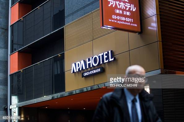 A man walks past the entrance of an APA hotel in central Tokyo on January 20 2017 Japanese organisers of next month's Asian Winter Games in Sapporo...