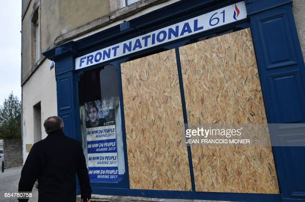 A man walks past the front of the premises of French farright Front National party which was damaged following a fire of criminal origin in the night...