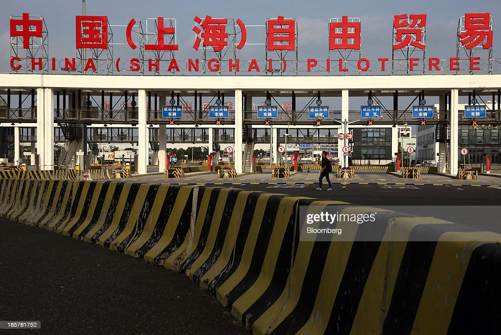 A man walks past the gate to China (Shanghai) Pilot Free Trade Zone's Pudong free trade zone in Shanghai, China, on Thursday, Oct. 24, 2013. The area is a testing ground for free-market policies that Premier Li Keqiang has signaled he may later implement more broadly in the worldÕs second-largest economy. Photographer: Tomohiro Ohsumi/Bloomberg via Getty Images