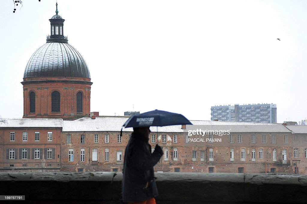 A man walks past the Hotel Dieu on January 20, 2013 in Toulouse southern France, after heavy snow falls. AFP PHOTO PHOTO / PASCAL PAVANI