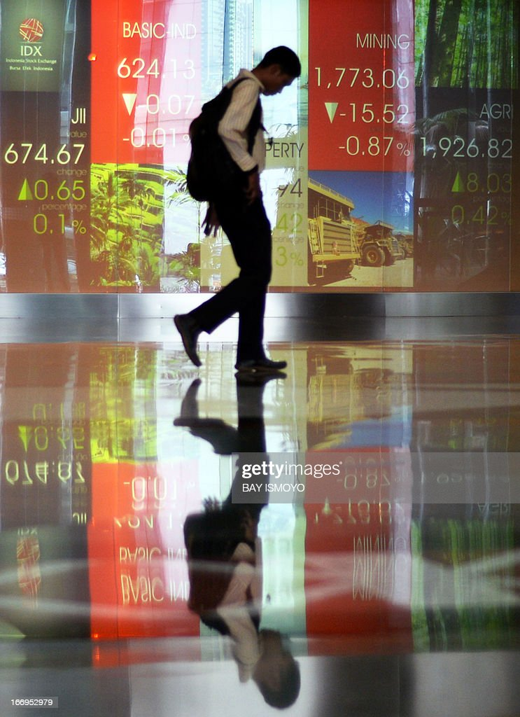 A man walks past the Jakarta Stock Exchange stocks display in Jakarta on April 19, 2013. According to local reports hopes that the government will raise the subsidized fuel price to bring down the budget deficit has helped the Jakarta composite index advance in the past few days. AFP PHOTO / Bay ISMOYO