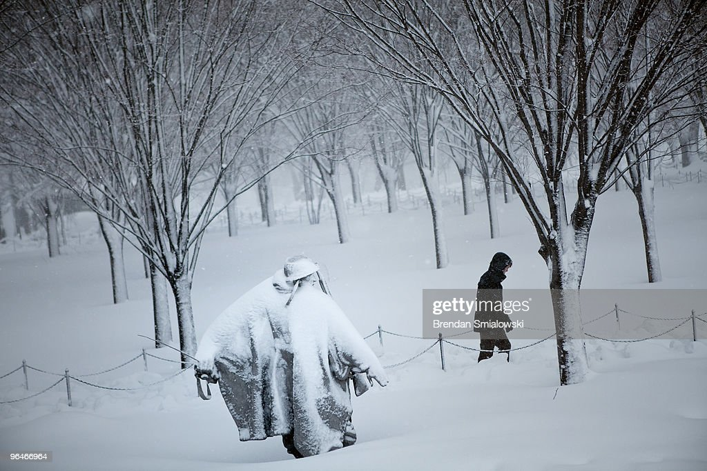 A man walks past the Korean War Memorial during a snow storm February 6 2010 in Washington DC A record setting snowstorm has hit the Washington DC...