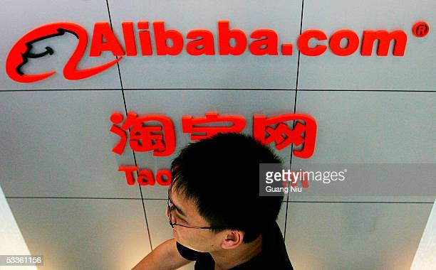 A man walks past the logo of Alibaba technology Co Lth on August 12 2005 in Beijing China Yahoo Inc signed a deal to buy 40 percent of Alibabacom for...