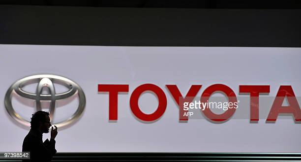 A man walks past the logo of Japanese car manufacturer Toyota at the 80th Geneva International Motor Show at Palexpo in Geneva on March 3 2010 Global...