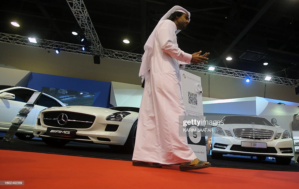 A Man walks past the Mercedes-Benz stand during the third International Qatar Auto Show on January 28, 2013 in Doha. AFP PHOTO / AL-WATAN DOHA / KARIM JAAFAR == QATAR OUT ==