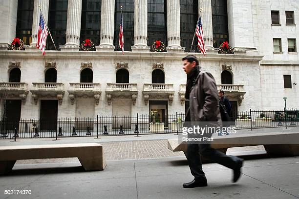 A man walks past the New York Stock Exchange on Wall Street and Exchange Streets on December 21 2015 in New York City The Dow Jones industrial...