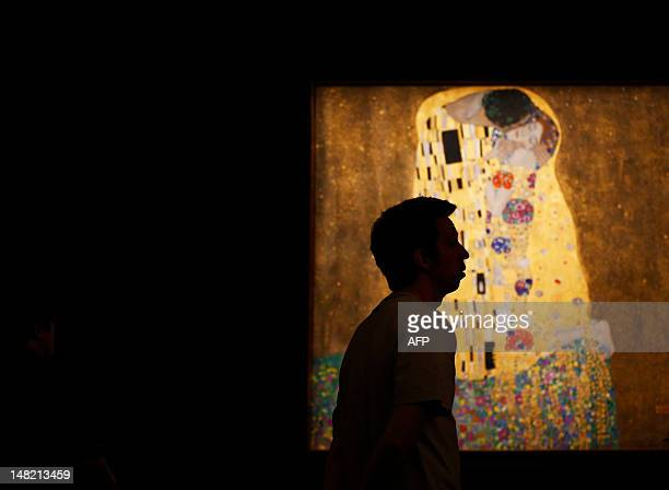 A man walks past the painting 'The Kiss' by Austrian artist Gustav Klimt at the Belvedere Palace in Vienna on July 12 2012 Vienna's Belvedere Museum...