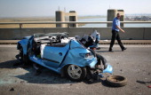 A man walks past the remains of a car involved in a major traffic accident on the A249 Sheppey crossing bridge in Kent on September 5 2013 in Isle of...