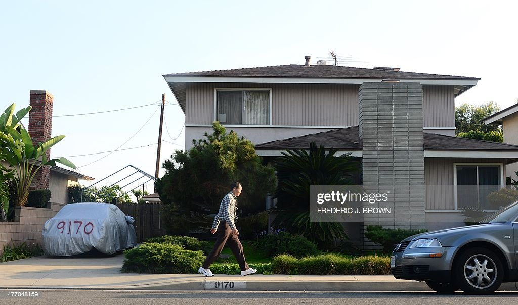 A man walks past the reported home of 'Satoshi Nakamoto' in Temple City, east of Los Angeles, California on March 6, 2014. After years of speculation, the true identity of 'Satoshi Nakamoto,' the mysterious person or group behind the Bitcoin revolution, appeared to have been revealed by Newsweek earlier in the day, who's reporter tracked down the 64-year-old physicist living under the name Dorian S. Nakamoto in a modest two-story house in suburban Los Angeles. Nakamoto did not admit to being behind the phenomenon that, since its 2009 launch, has been hailed as a financial revolution despite scandals over its use in the drugs trade and money-laundering and he called the police when the magazine's reporter knocked on his door. AFP PHOTO/Frederic J. BROWN