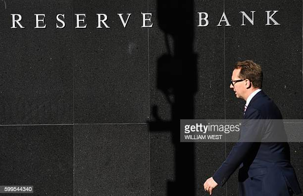 A man walks past the Reserve Bank of Australia sign in Sydney on September 6 as Australia's central bank held interest rates steady at a record low...