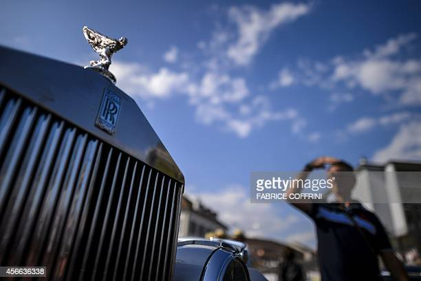 A man walks past the RollsRoyce iconic mascot 'Spirit of Ecstacy' on the bonnet of a RollsRoyce during the 23rd'Swiss Classic British Car Meeting' on...