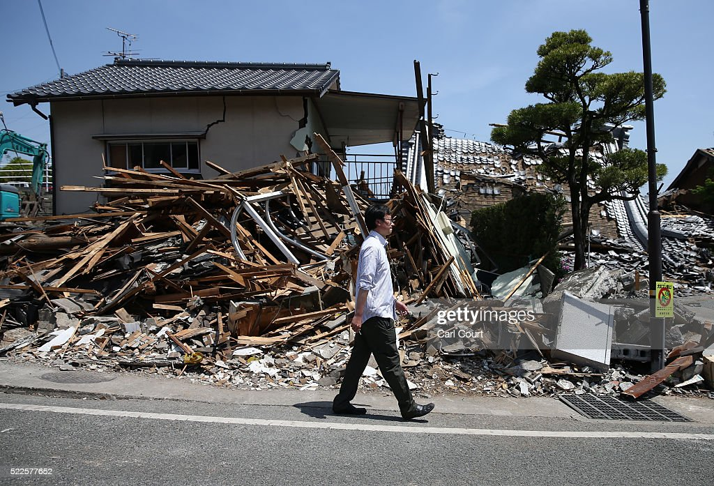 A man walks past the rubble of a collapsed house following an earthquake on April 20 2016 in Mashiki near Kumamoto Japan As of April 20 48 people...