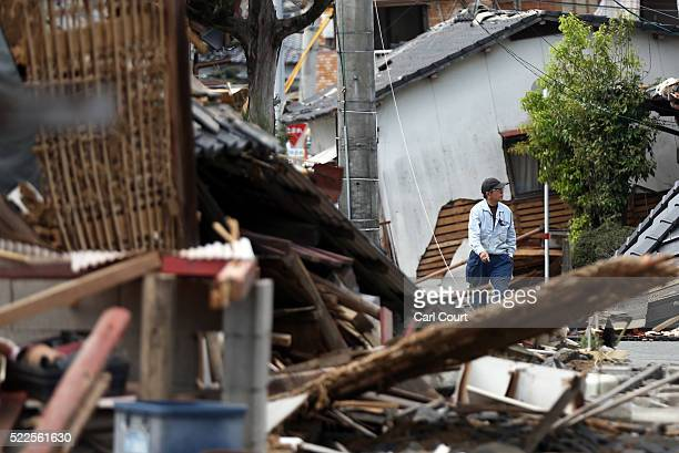 A man walks past the rubble of collapsed houses following an earthquake on April 20 2016 in Mashiki near Kumamoto Japan As of April 20 48 people were...