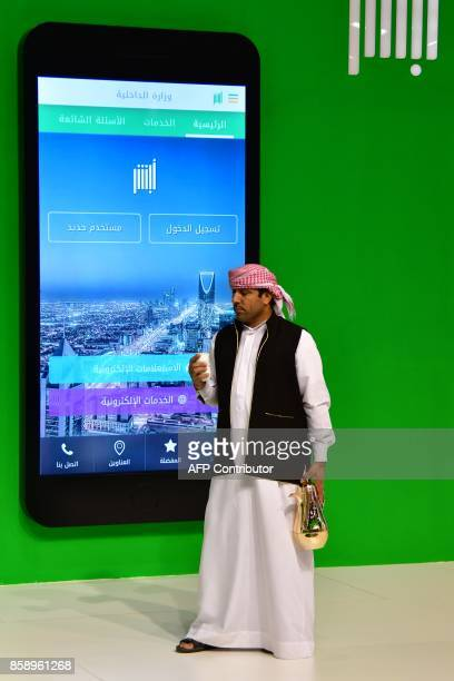 A man walks past the Ruyaa 2030 pavilion at the Gitex 2017 exhibition at the Dubai World Trade Center in Dubai on October 8 2017 / AFP PHOTO /...