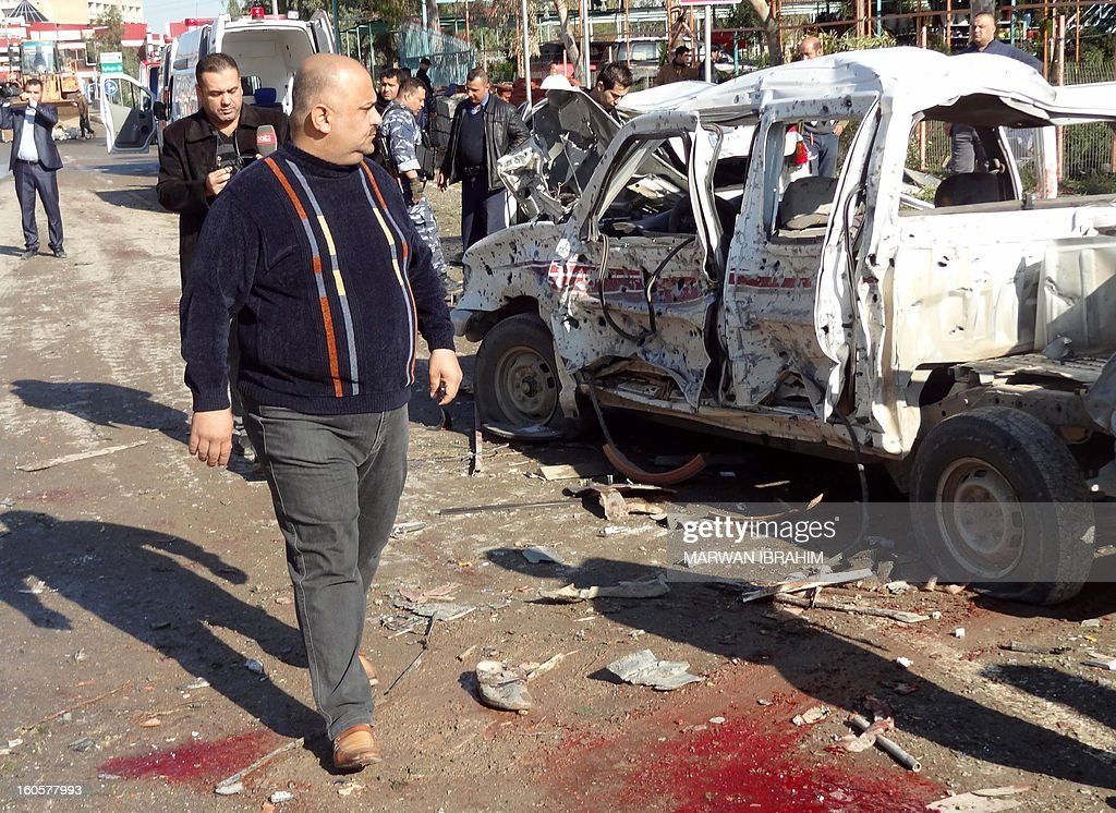 A man walks past the scene after a car bombing followed by an assault by grenade-throwing gunmen on a police headquarters in a disputed northern city of Kirkuk, on February 3, 2013, killing some 30 people. The vehicle that was detonated in the center of the city was painted to appear as though it was a police car, and the militants who sought to seize the compound were dressed as policemen, witnesses said. AFP PHOTO/MARWAN IBRAHIM