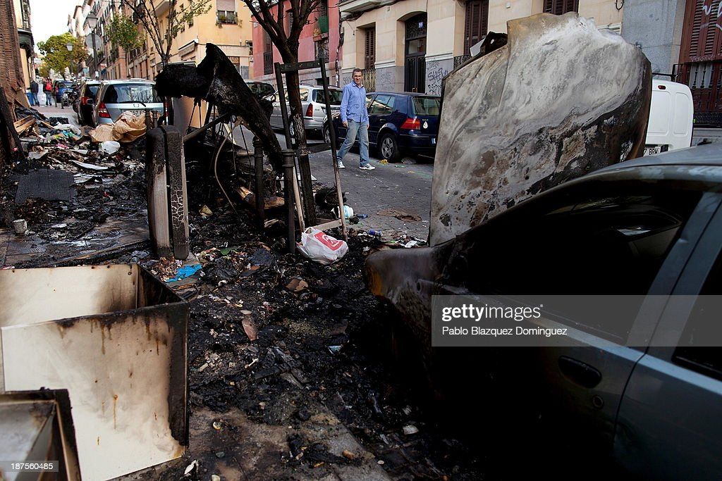A man walks past the scene of an earlier fire caused by overflowing bins which had been set alight in the city centre on November 10, 2013 in Madrid, Spain. Street cleaners, garbage collectors and public park gardeners working for Madrid city council started an indefinite strike six days ago. Franchise firms which employ them plan to axe more than 1,000 jobs and those who will remain will have to face working for a 40 percent cut in their wages.