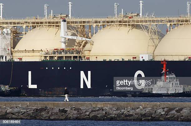 A man walks past the Shahamah liquefied natural gas tanker sitting berthed at Tokyo Electric Power Co's Futtsu gasfired thermal power plant in Futtsu...