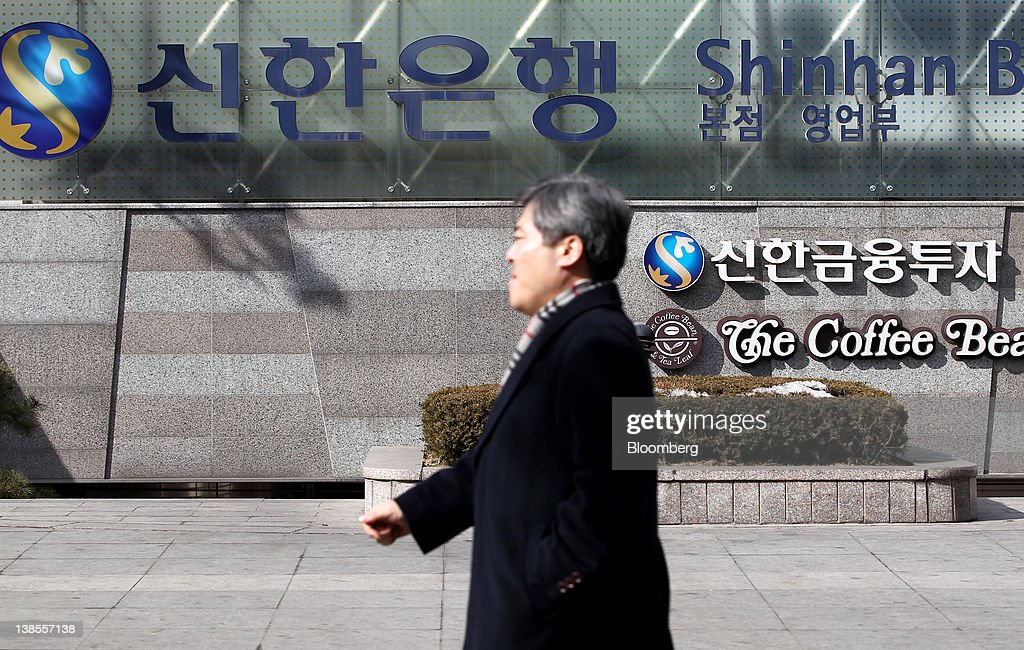 A man walks past the Shinhan Bank headquarters in Seoul, South Korea, on Thursday, Feb. 9, 2012. Shinhan Financial Group Inc., South Korea's largest financial services group by market value, said profit dropped 13 percent in the fourth quarter as the company set aside more provisions for bad debts. Photographer: SeongJoon Cho/Bloomberg via Getty Images