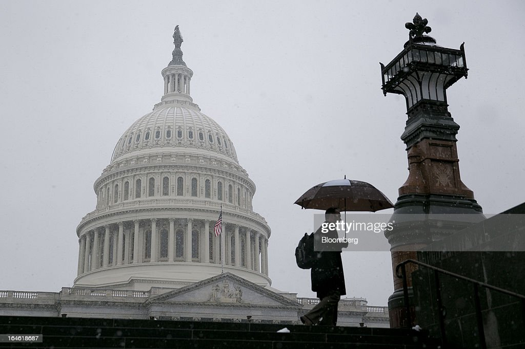 A man walks past the U.S. Capitol holding an umbrella in Washington, D.C., U.S., on Monday, March 25, 2013. An early spring snowstorm tied up air traffic along the U.S. East Coast, threatening to bring 3 inches (7.6 centimeters) of slushy snow to the large cities from Washington to New York. Photographer: Andrew Harrer/Bloomberg via Getty Images