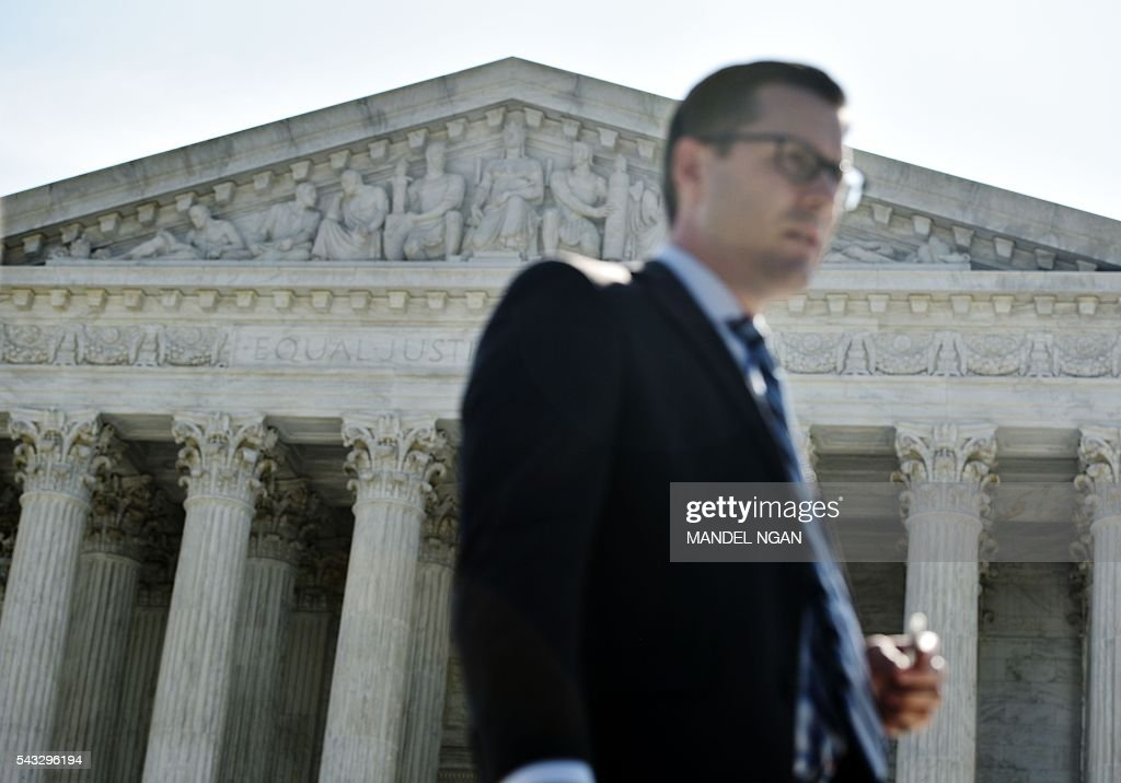 A man walks past the US Supreme Court ahead of a ruling on abortion clinic restrictions on June 27, 2016 in Washington, DC. In a case with far-reaching implications for millions of women across the United States, the court ruled 5-3 to strike down measures which activists say have forced more than half of Texas's abortion clinics to close. / AFP / MANDEL