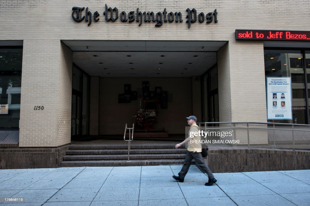 A man walks past The Washington Post building on August 5, 2013 in Washington, DC, after it was announced that Amazon.com founder and CEO Jeff Bezos had agreed to purchase the Post for USD 250 million. Multi-billionaire Bezos, who created Amazon, which has soared in a few years to a dominant position in online retailing, said he was buying the Post in his personal capacity and hoped to shepherd it through the evolution away from traditional newsprint. AFP PHOTO/Brendan SMIALOWSKI