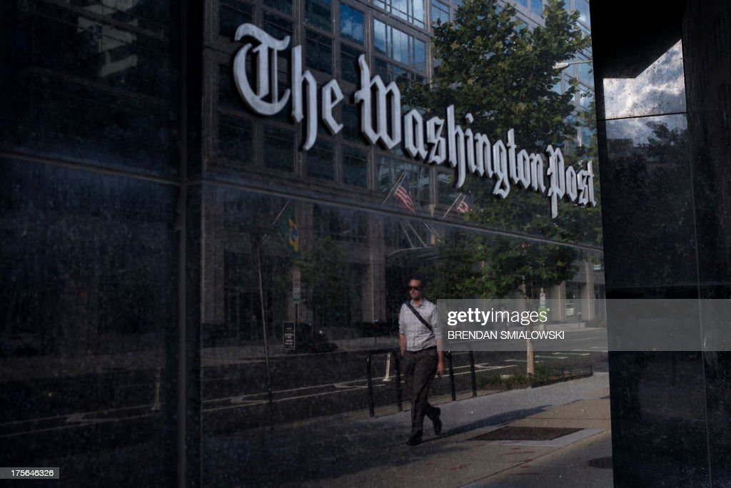 A man walks past The Washington Post on August 5, 2013 in Washington, DC after it was announced that Amazon.com founder and CEO Jeff Bezos had agreed to purchase the Post for USD 250 million. Multi-billionaire Bezos, who created Amazon, which has soared in a few years to a dominant position in online retailing, said he was buying the Post in his personal capacity and hoped to shepherd it through the evolution away from traditional newsprint. AFP PHOTO/Brendan SMIALOWSKI