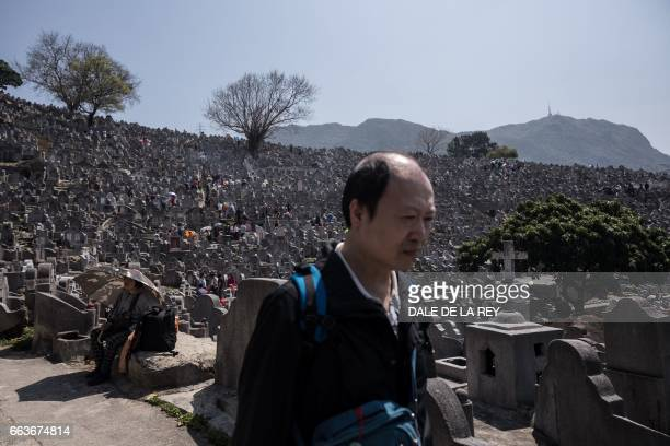 A man walks past tombstones at a cemetery ahead of the Ching Ming Festival or gravesweeping day in Hong Kong on April 2 2017 Visiting the graves of...