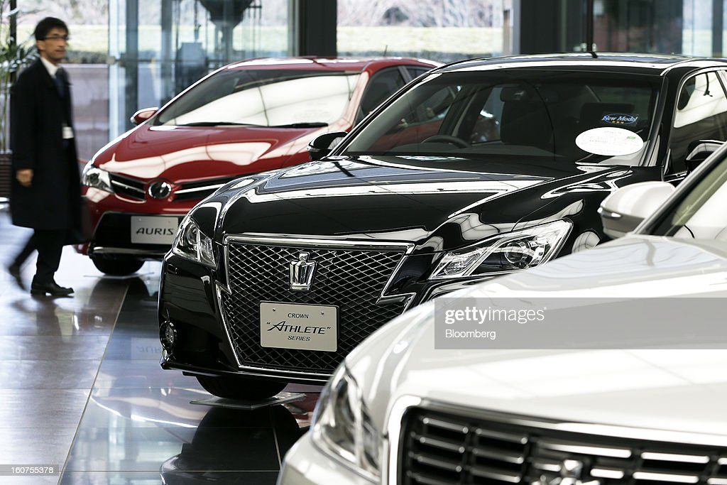 A man walks past Toyota Motor Corp.'s Auris compact vehicle, left, and Crown Athlete sedan, center, displayed at the company's headquarters in Tokyo, Japan, on Tuesday, Feb. 5, 2013. Toyota, the world's biggest carmaker, raised its profit forecast after the yen weakened more than any other currency, raising the value of Japanese cars sold overseas. Photographer: Kiyoshi Ota/Bloomberg via Getty Images