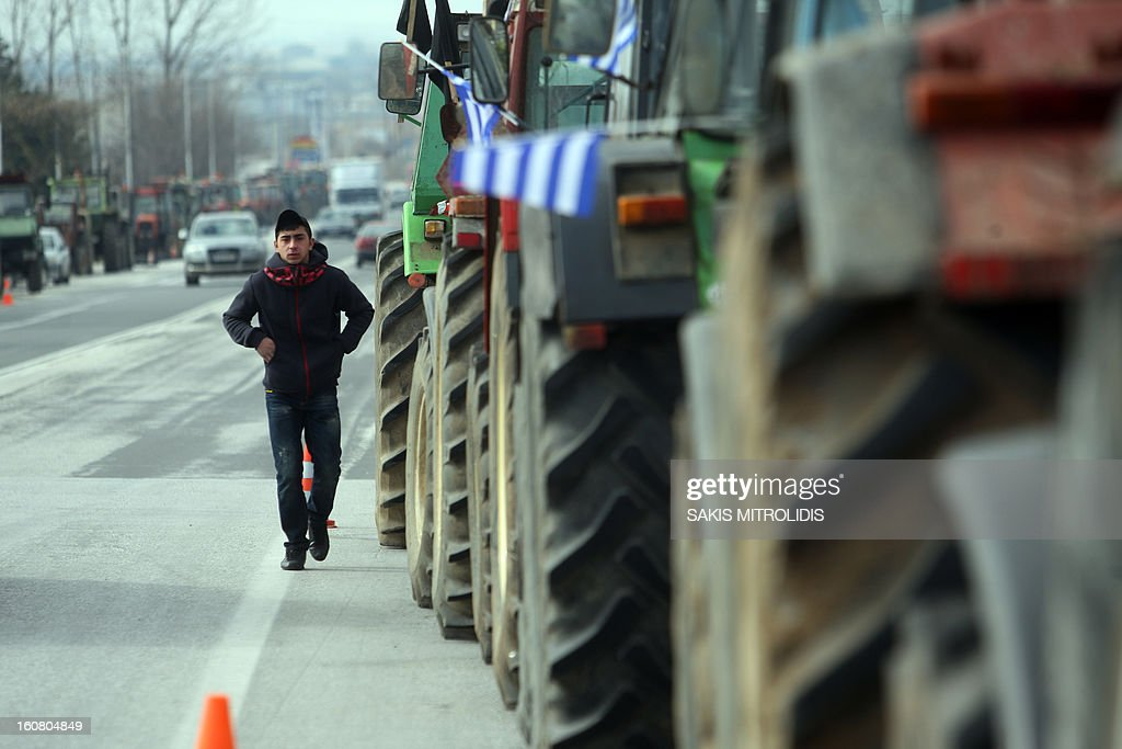 A man walks past tractors that farmers have parked along major motorways in Serres, north of Athens, on February 6, 2013, to protest against the cost of raw material they need for their production, such as petrol.