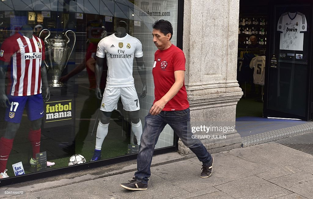 A man walks past two jerseys of the Real Madrid and Atletico de Madrid football clubs displayed in a shopwindow at the Puerta del Sol square in Madrid on May 25, 2015. The two football teams of Madrid will play the UEFA Champions League final in Milan on May 28, 2016. / AFP / GERARD