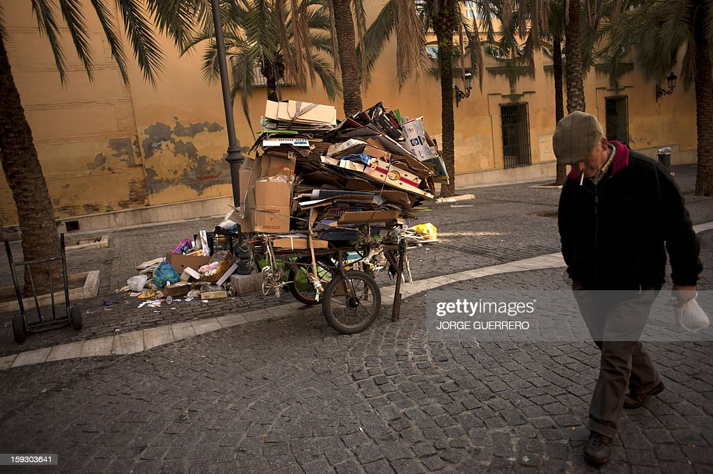 A man walks past uncollected rubbish in a street of Granada on January 11, 2013. Rubbish collectors have been on strike in the municipality of Granada to protest against the austerity cuts imposed by the town hall. AFP PHOTO / JORGE GUERRERO