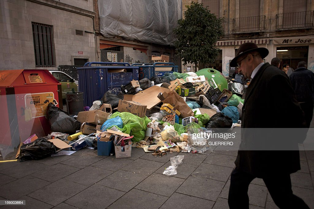A man walks past uncollected rubbish in a street of Granada on January 11, 2013. Rubbish collectors have been on strike in the municipality of Granada to protest against the austerity cuts imposed by the town hall.