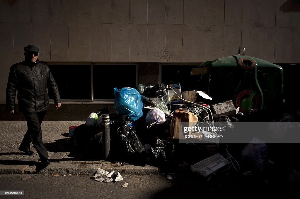 A man walks past uncollected rubbish in a street of Sevilla on February 4, 2013. Rubbish collectors have been on strike in the municipality of Sevilla to protest against the austerity cuts imposed by the town hall.