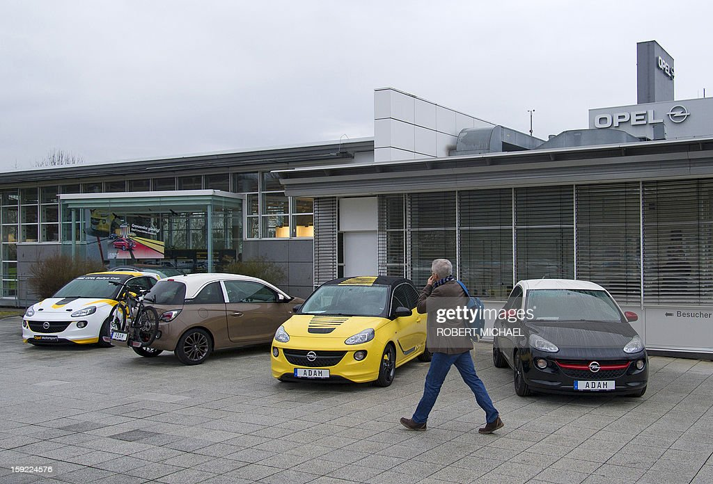 A man walks past various models of an Opel Ada, parked infront of the Opel plant in Eisenach, eastern Germany on January 10, 2013. The new Opel model will be produced as of January 10, 2013 at the Eisenach Opel plant and is intended to attract young automobile drivers in cities. Opel has already received 16 000 orders for the Adam.