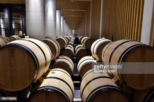 A man walks past wine barrel in the wine cellar of the Chateau Pedesclaux in Pauillac on March 31 2017 Famous architects transform the Bordeaux' wine...