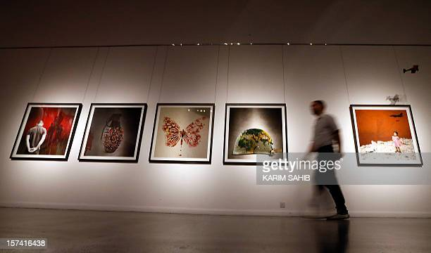 A man walks past work by digital artist Tammam Azzam part of an exhibition titled 'The Syrian Museum' on show in Dubai on November 29 2012 A popular...