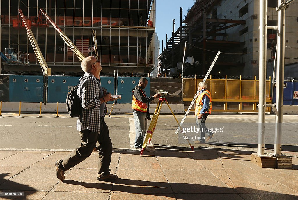 A man walks past workers in front of the World Trade Center site under construction on October 22, 2012 in New York City. The Census Bureau reported last month that between 2000 and 2010 the downtown population grew by nearly 40,000 people, in spite of the September 11 terrorist attacks at the World Trade Center. One World Trade Center is scheduled to open in 2014 at the symbolic height of 1,776 feet and will be the tallest building in the Western Hemisphere.
