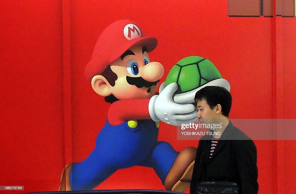 A man walks pat an advertisement for Japanese videogame maker Nintendo at a Tokyo electronics shop on October 30, 2013. Nintendo said on October 30 it swung back to profitability for the six months to September on a sharply weaker yen, but the Japanese videogames giant struggled with tepid sales of its Wii U console. AFP PHOTO / Yoshikazu TSUNO
