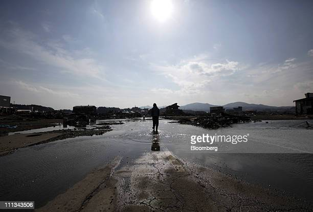 A man walks through a damaged road in Kesennuma City Miyagi Prefecture Japan on Friday April 1 2011 Japan begins forging a road map for recovery from...