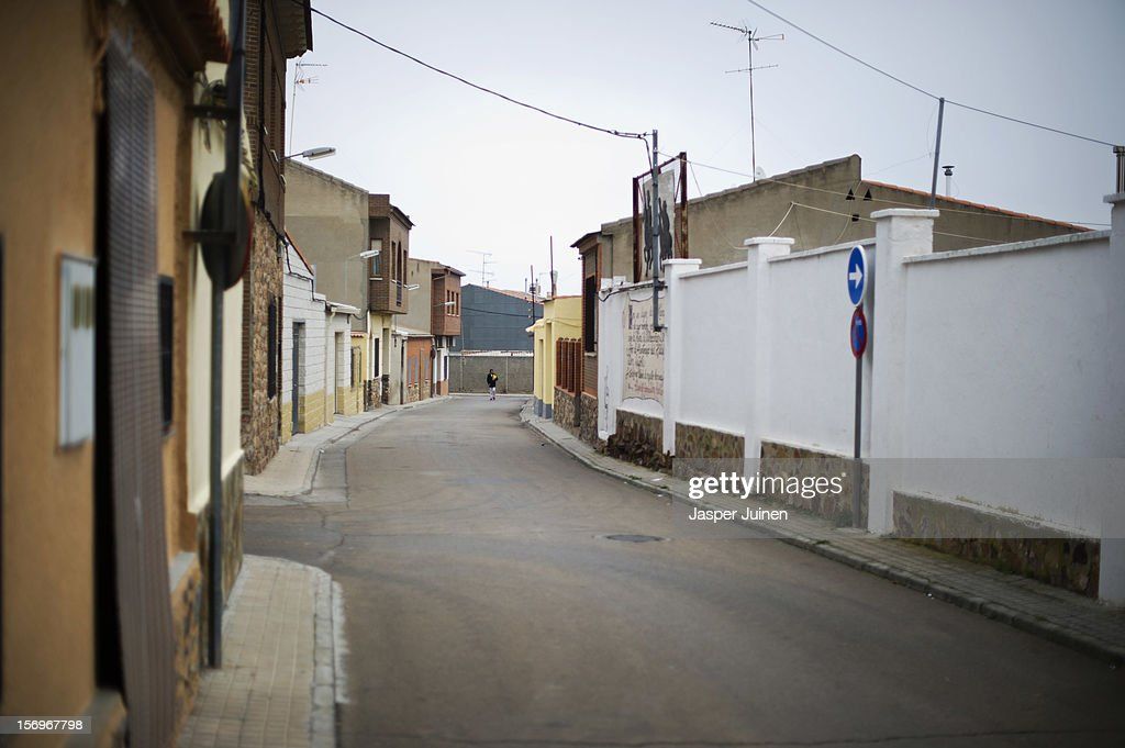 A man walks through a deserted street on November 23, 2012 in Villacanas, Spain. During the boom years, where in its peak Spain built some 800,000 houses a year accompanied by the manufacturing of millions of wooden doors where needed, the people of Villacanas were part of Spain's middle class enjoying high wages and permanent jobs. During the construction boom years the majority of the doors used within these new developments were made in this small industrial town. Approximately seven million doors a year were once assembled here and the factory employed a workforce of almost 5700 people, but the town is now left almost desolate with the Villacanas industrial park now empty and redundant. With Spain in the grip of recession and the housing bubble burst, Villacanas is typical of many former buoyant industrial Spanish towns now struggling with huge unemployment problems.