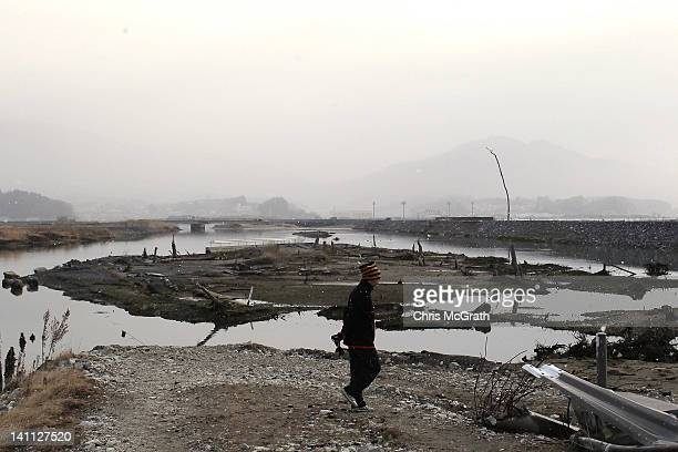 A man walks through a destroyed area near the seaside on March 11 2012 in Rikuzentakata Japan Today marks the one year anniversary of the 90...