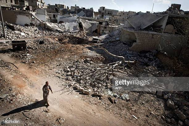 A man walks through a destroyed residential area of the Syrian city of Saraqib southwest of Aleppo on September 9 following repeated airstrikes by...