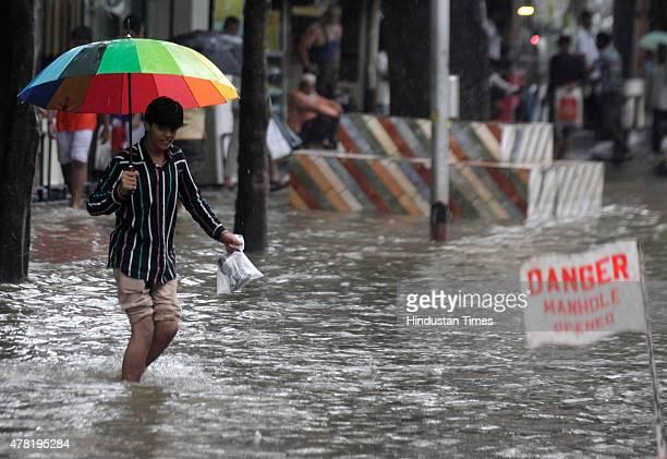 A man walks through a flooded street as a sign read danger after heavy rain at Hindamata Dadar on June 23 2015 in Mumbai India Heavy rainfall across...