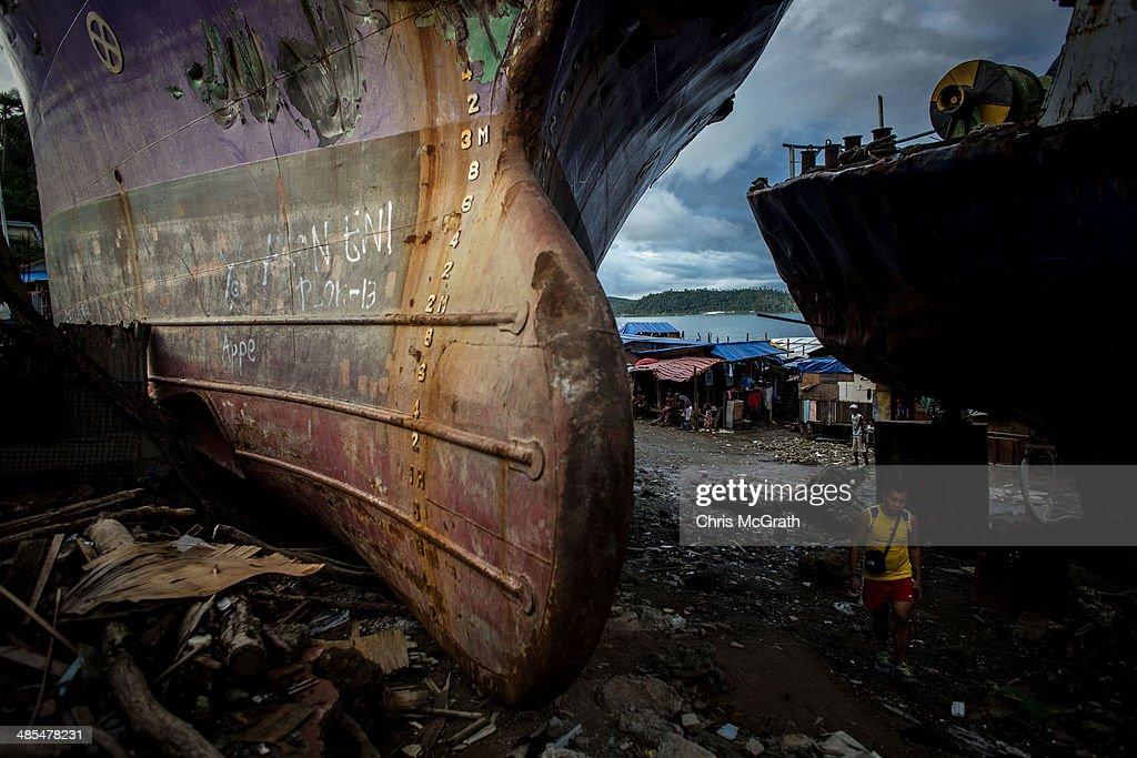 A man walks through a gap between three large ships that were grounded by Typhoon Haiyan on April 18, 2014 in Tacloban, Leyte, Philippines. People continue to rebuild their lives five months after Typhoon Haiyan struck the coast on November 8, 2013, leaving more than 6000 dead and many more homeless. Although many businesses and services are functioning, electricity and housing continue to be the main issues, with many residents still living in temporary housing conditions due to 'No Build' areas preventing them from rebuilding their homes. This week marks Holy Week across the Philippines and will see many people attending religious activities.